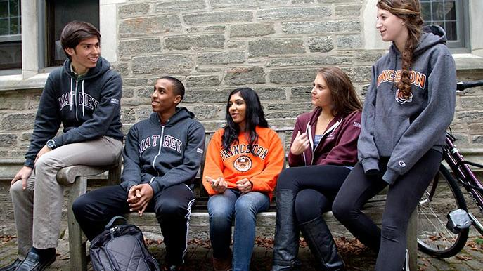 Group of students sitting on a bench talking